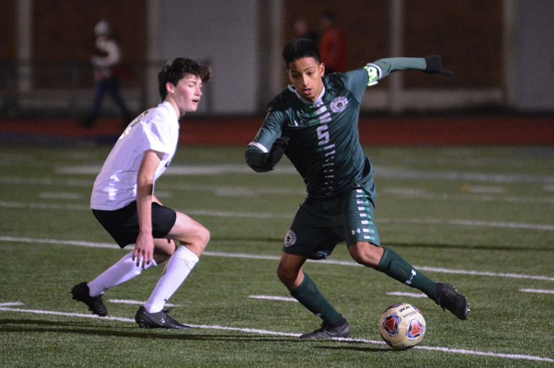 PMG PHOTO: DAVID BALL - Reynolds Pedro Bodo Calderon moves around a Tualatin player in the midfield during Wednesdays 2-0 playoff win.
