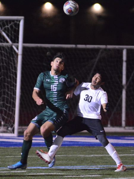 PMG PHOTO: DAVID BALL - Reynolds center-back Angel Vides (16) battles for position with Tualatins Jose Hyre on a high ball played in front of the Raiders goal.