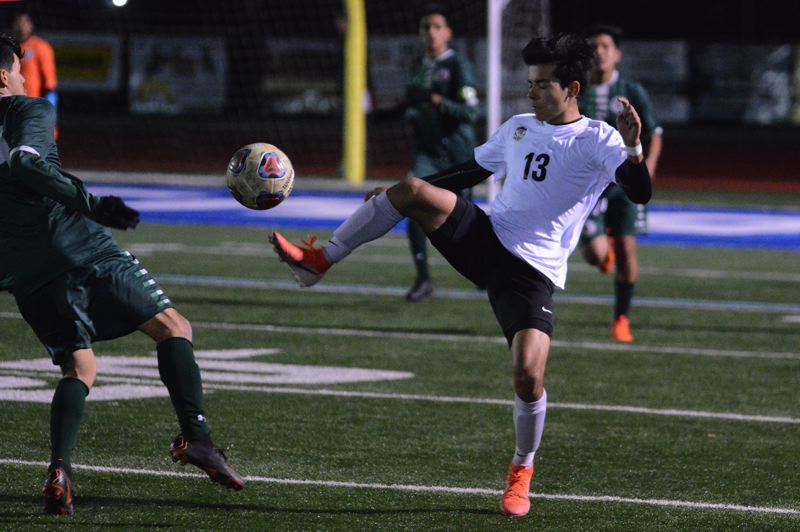 PMG PHOTO: DAVID BALL - Tualatins Remus Repcak plays a ball out of the air during the first half of Wednesdays 2-0 playoff loss to No. 2-seed Reynolds.