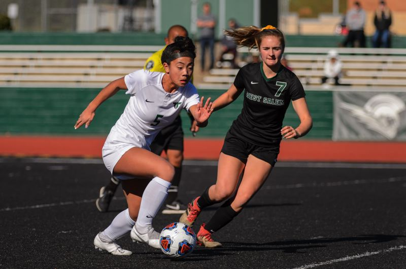 COURTESY PHOTO: CHRISTOPHER GERMANO - Tigard High School freshman Jaiden Riodil (left) races with the ball with West Salem junior Jolie Jones during the state playoff first-round match.