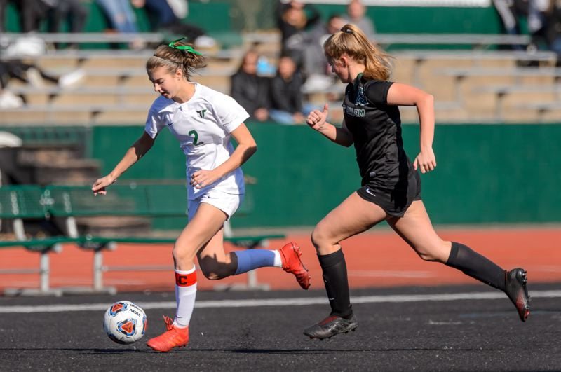 COURTESY PHOTO: CHRISTOPHER GERMANO - Tigard High School junior forward Lydia Emory races with the ball ahead of a West Salem defender during the teams' state playoff first-round match.