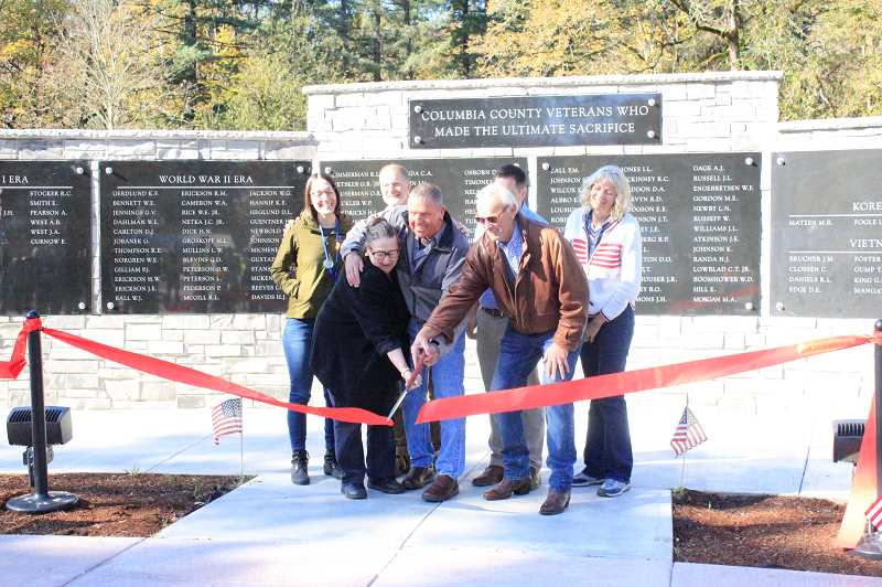 PHOTO COURTESY OF NICOLE THILL-PACHECO - Scappoose Democratic Sen. Betsy Johnson, VFW Post 1440's Gene Hester and St. Helens City Councilor Doug Morten jointly direct ceremonial scissors and cut the ribbon to open the newly expanded Veterans Memorial at McCormick Park in St. Helens on Friday, Nov. 1. All pictured, from left: Jenny Dimsho, St. Helens associate planner; Johnson; Andrew Niemi, Lower Columbia Engineering; Hester; Moten; Brandon Sundeen (behind Morten) of Columbia County Museum Association; and Sue Nelson, St. Helens engineering director.