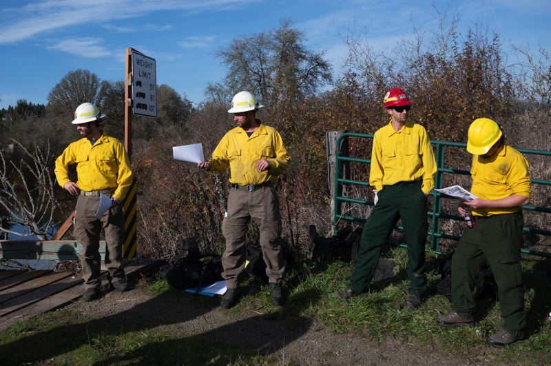 PMG PHOTO: CHRISTOPHER OERTELL - Burn boss Jeremiah Maghan of the U.S. Fish & Wildlife Service, second from left, leads a briefing Thursday, Nov. 7, before a pair of prescribed burns at the Wapato Lake National Wildlife Refuge.