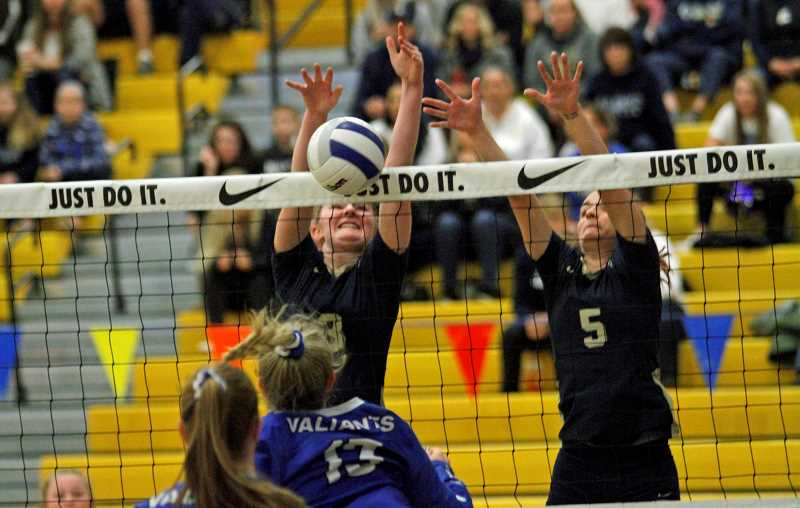 PMG PHOTO: WADE EVANSON - Banks' Kinely Hoag (left) and Haylee Jackson (right) go up to block a Valley Catholic spike during the Braves' state tournament game against the Valiants Friday morning, Nov. 8, at Forest Grove High School.