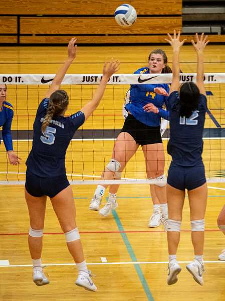 LON AUSTIN/CENTRAL OREGONIAN - Kenna Woodward plays a shot between a pair of Corvallis blockers during Crook County's quarterfinal loss to the Spartans. Woodward led the Cowgirls in kills with nine.