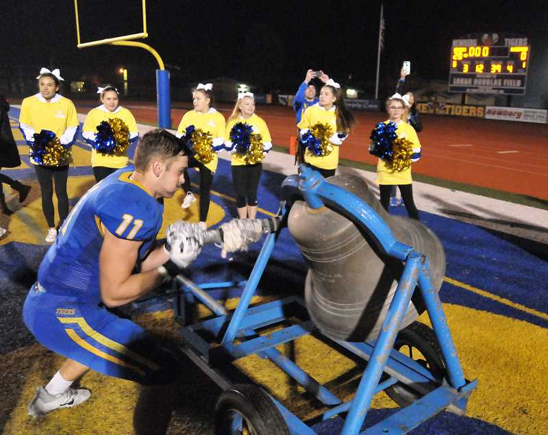 GRAPHIC PHOTO: GARY ALLEN - The Tigers embrace tradition and ring the school bell upon their defeat of South Medford on Friday evening at Loran Douglas Field.