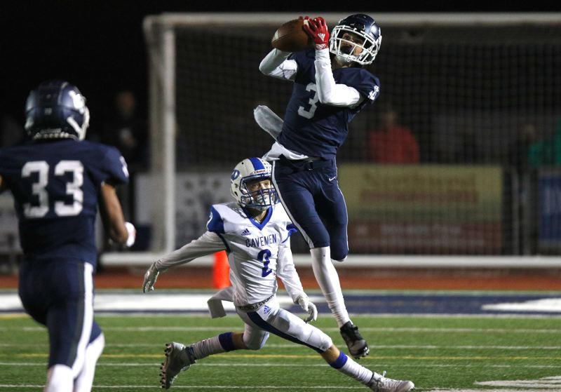PMG PHOTO: JONATHAN HOUSE - Lake Oswego senior wide receiver Joe Hutson makes a leaping catch during his team's first-round win over Grants Pass at Lake Oswego High School on Friday, Nov. 8.