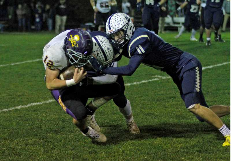 PMG PHOTO: WADE EVANSON - Banks' Jacob Slifk puts a hit on Marshfield's Ezra Waterman during the Braves' first round playoff game against the Pirates Friday, Nov. 8, at Banks High School.