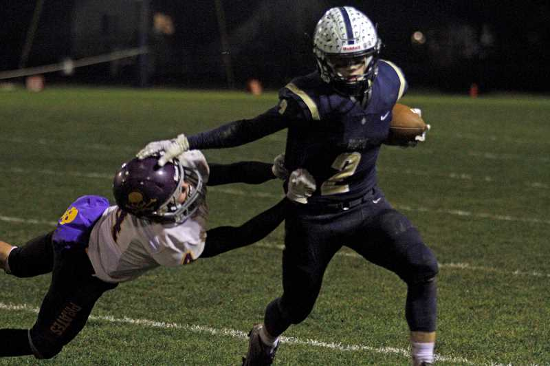 PMG PHOTO: WADE EVANSON - Banks' Jarred Evans stiff arms a Marshfield defender during the Braves' first round playoff game against the Pirates Friday, Nov. 8, at Banks High School.