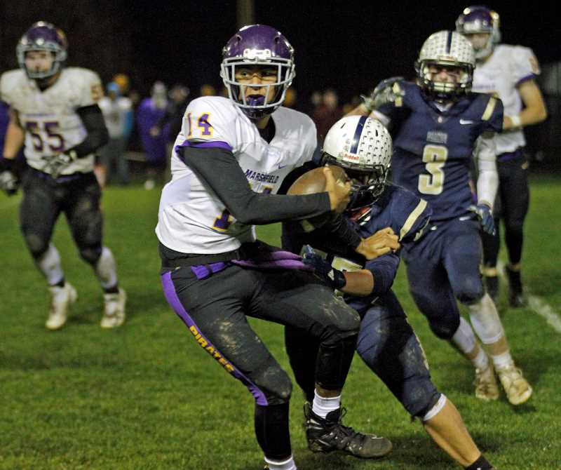 PMG PHOTO: WADE EVANSON - Marshfield quarterback Dom Montiel is sacked by a swarming Banks defense during the Pirates' first round playoff game against the Braves Friday, Nov. 8, at Banks High School.