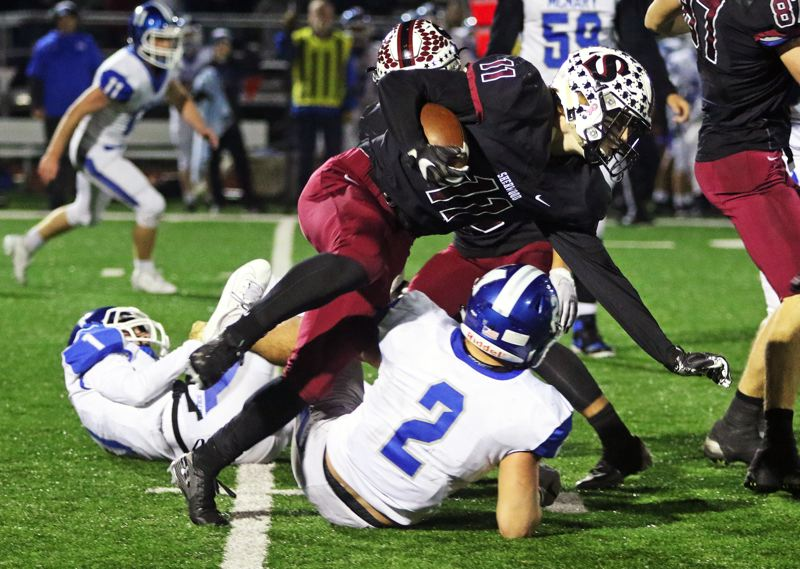 PMG PHOTO: DAN BROOD - Sherwood High School junior running back Clay Peden (11) tries to power his way for extra yardage during the Bowmen's 49-7 win over McNary in Friday's Class 6A first-round state playoff game.