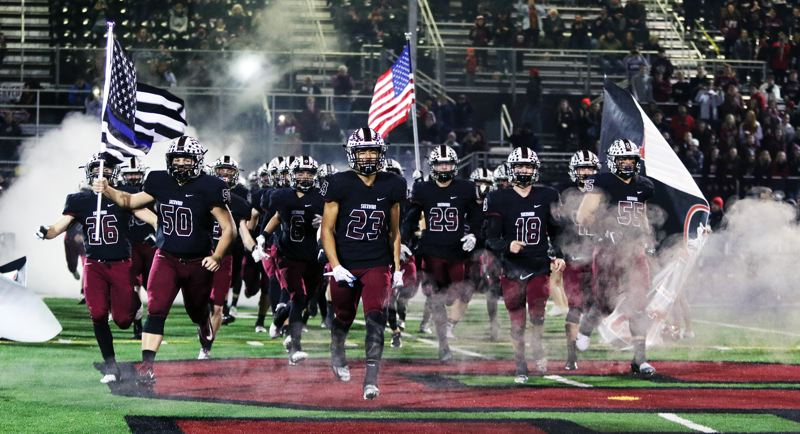 PMG PHOTO: DAN BROOD - The Sherwood High School football team takes the field prior to Friday's Class 6A state playoff second-round game against McNary. The Bowmen won 49-7.