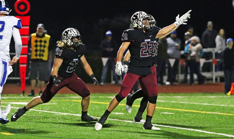 PMG PHOTO: DAN BROOD - Sherwood junior Jack Causey (21) and junior Holden Gilbert celebrate following a Bowmen goal-line stand in the team's 49-7 state playoff win over McNary.