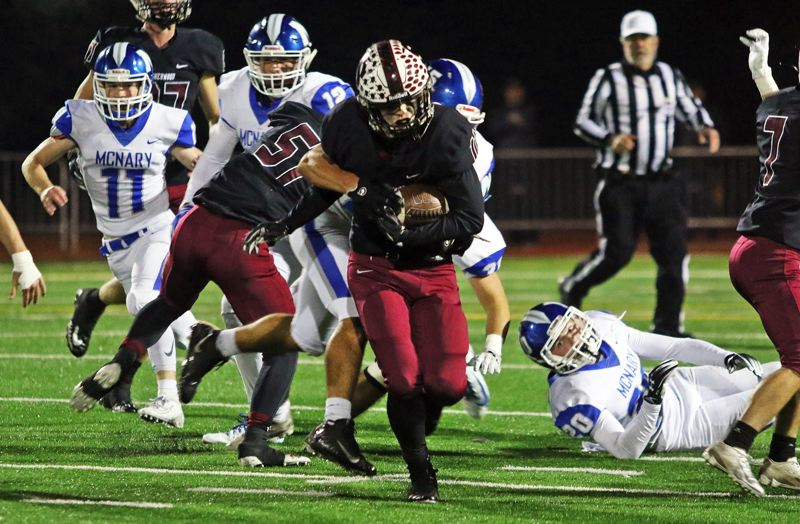 PMG PHOTO: DAN BROOD - Sherwood High School junior Clay Peden tries to break into the clear, behind a block by senior Ian Glenn, during the Bowmen's 49-7 state playoff win over McNary on Friday.