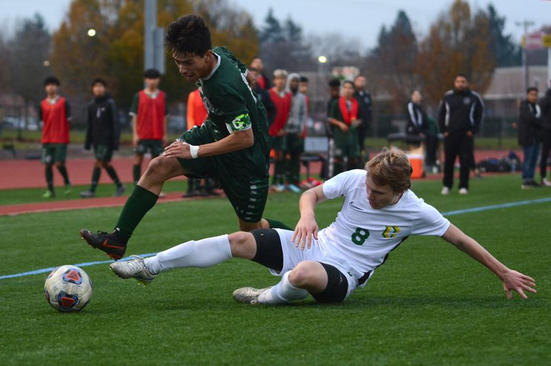 PMG PHOTO: DAVID BALL - Cleveland defender Seb Buscaglia slides down to take the ball off the foot of Reynolds' Gerardo Mejia during the Warriors' 6-4 quarterfinal win Saturday.