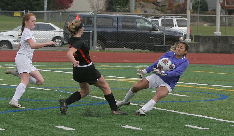 PMG PHOTO: JIM BESEDA - Woodburn goalkeeper Carla Zamora (right) blocks a shot by Gladstone's Rhyli Grim during the first half, helping lead the Bulldogs to a 2-0 road win in Saturday's OSAA 4A girls soccer quarterfinals.