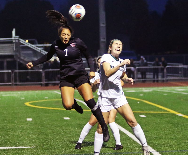 PMG PHOTO: DAN BROOD - Sherwood High School senior Loma McNeese (7) goes up high to get her head on the ball during the Lady Bowmen's state playoff quarterfinal match with West Salem.