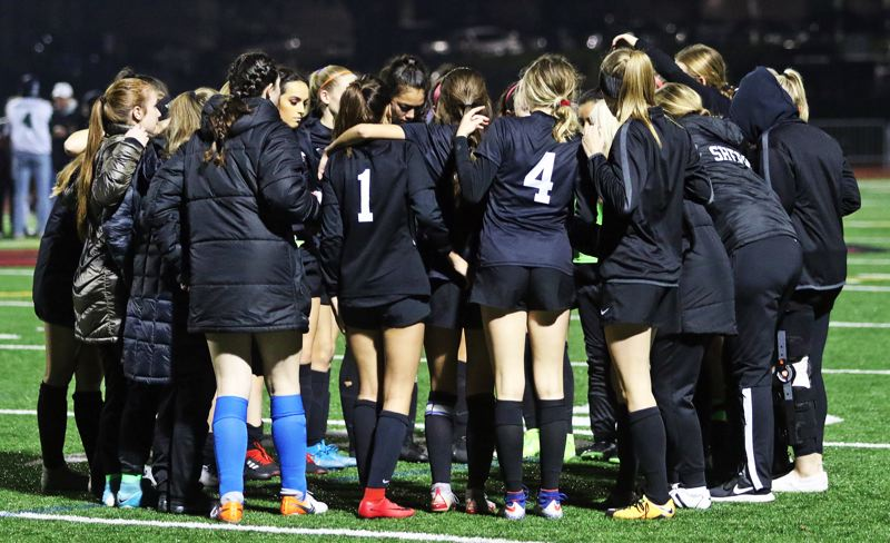 PMG PHOTO: DAN BROOD - Sherwood High School girls soccer players and coaches gather together following the 2-1 loss to West Salem in the Class 6A state playoff quarterfinal match.