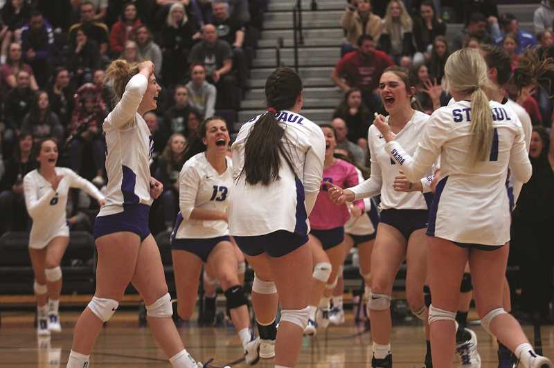 PMG PHOTO: PHIL HAWKINS - The St. Paul Buckaroos celebrate game-point, securing the teams second consecutive 1A Volleyball State Championship against the Powder Valley Badgers on Saturday at Ridgeview High School in Redmond.