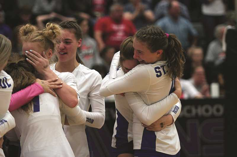 PMG PHOTO: PHIL HAWKINS - Senior Erin Counts (right) embraces freshman Annabelle Davidson following the teams state championship victory. Counts is one of four seniors on this years team, joined by Isabelle Wyss, Destiny Smith and Karlee Southerland.