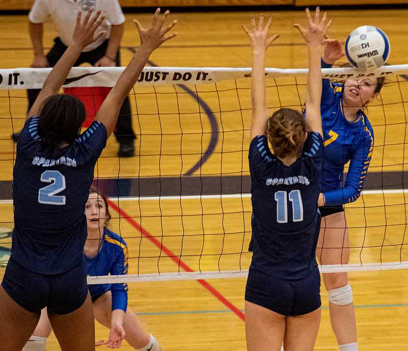 LON AUSTIN/CENTRAL OREGONIAN - Lily Cooper hits a shot over a pair of Corvallis blockers on Friday. Cooper finished with seven kills in the match, but the Spartans won in four sets. Crook County rebounded to win two games Saturday to finish in fourth place.