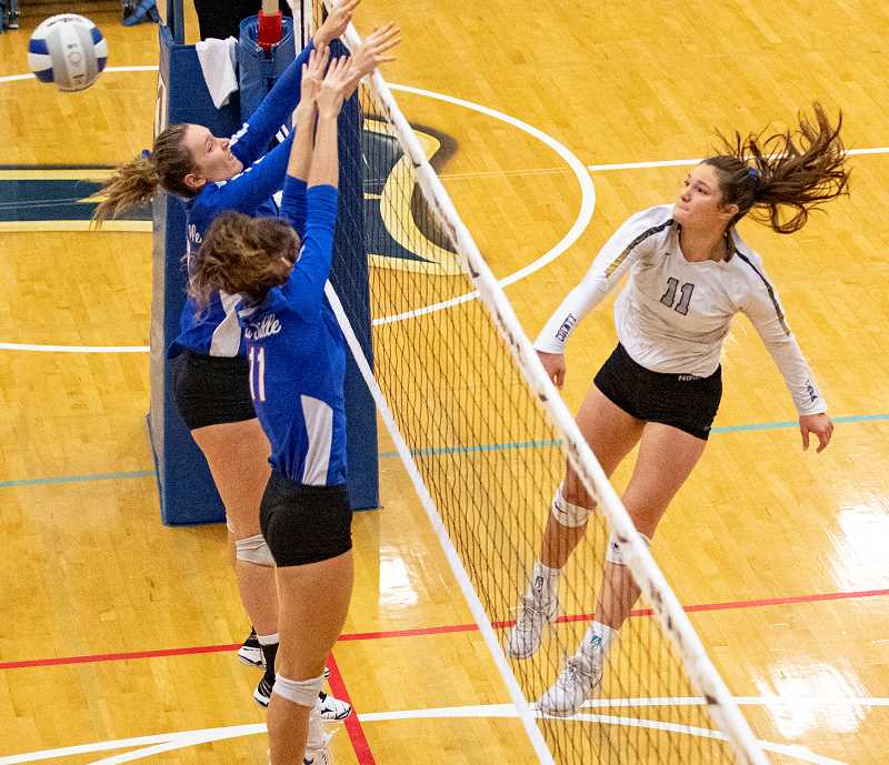 LON AUSTIN/CENTRAL OREGONIAN - Liz Barker blasts a shot past a pair of blockers from La Salle Prep Saturday morning in the first round of consolation. Barker had six kills in the match as the Cowgirls won in straight sets.