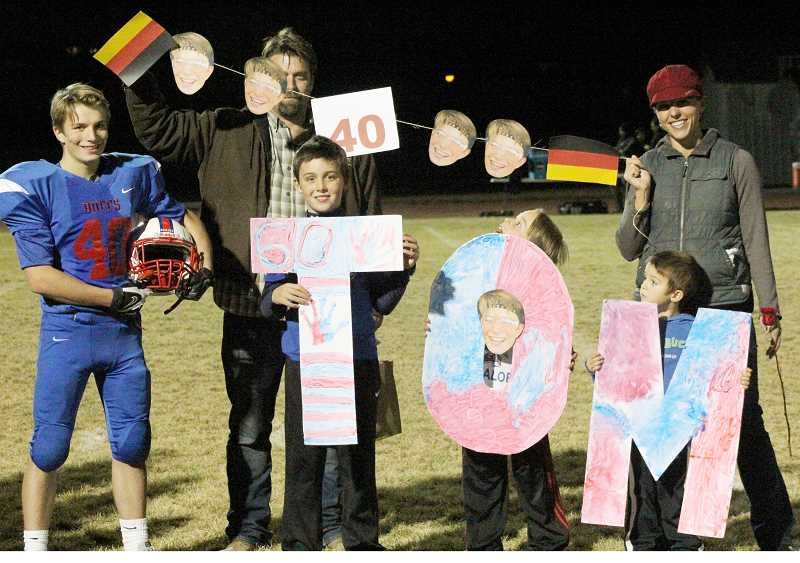 STEELE HAUGEN - Tom Kallenbach, left, a foreign exchange student from Germany, stands next to his host family, that of Jeff and Jamie Hurd, on Madras' senior night game Oct. 25. Kallenbach, who had never even watched a football game before, scored a touchdown against Salem Academy Nov. 1.