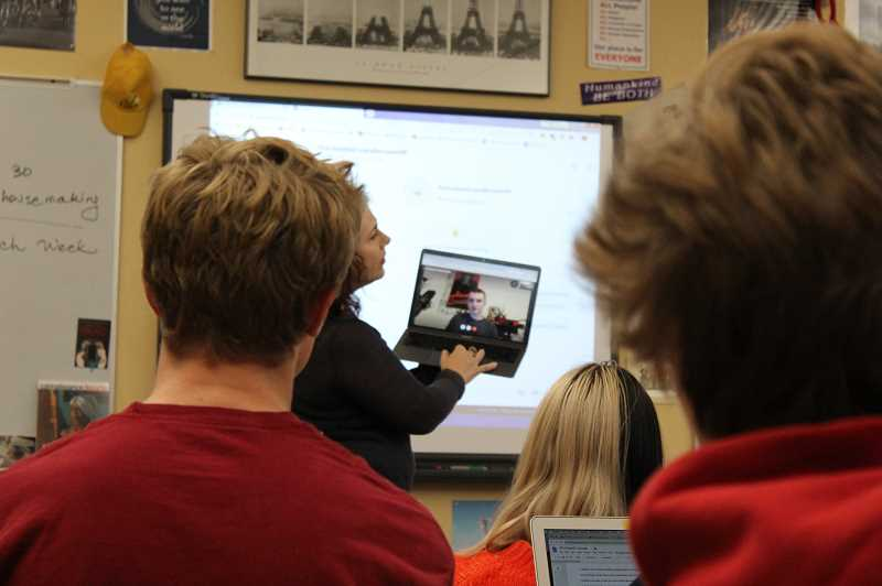 PMG PHOTO: ASIA ALVAREZ ZELLER  - Lisa Grimm holds up laptop to intorduce the class to author.