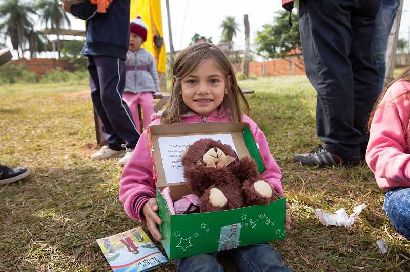 COURTESY OF SAMARITANS PURSE. - A child in Paraguay opens a package from Samaritans Purse, a Christian relief and evangelism organization.