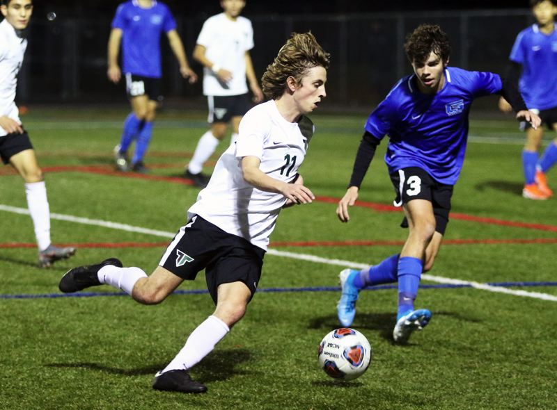 PMG PHOTO: DAN BROOD - Tigard High School senior Jacob Theodoroff (left) tries to move the ball upfield against Grant junior Nico Spathas during the teams' second-round state playoff match.
