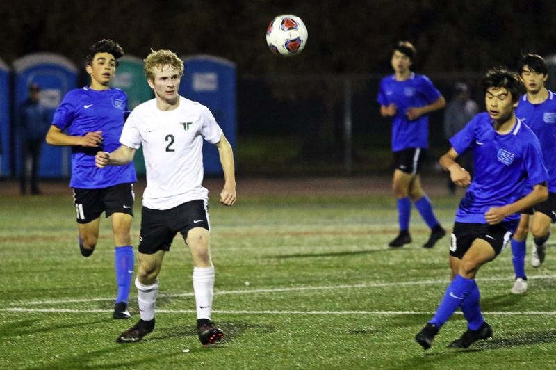 PMG PHOTO: DAN BROOD - Tigard High School junior Jack Hallam (2), in the middle of a group of Grant players, eyes the ball during last week's state playoff match held in Delta Park.