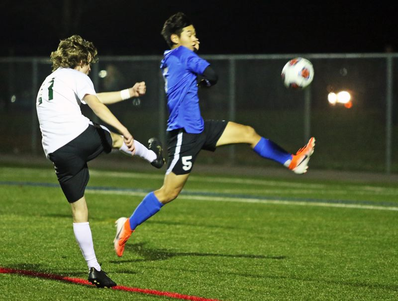 PMG PHOTO: DAN BROOD - Tigard High School senior Jacob Theodoroff (left) boots the ball past Grant senior Aaron Ha during last week's Class 6A state playoff match.