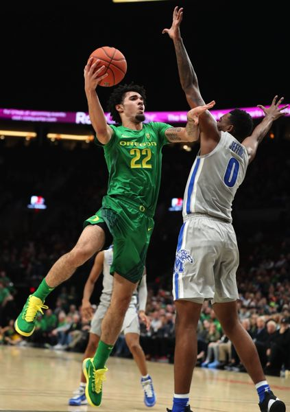 PMG PHOTO: JAIME VALDEZ - Oregon Ducks guard Addison Patterson shoots over Memphis Tigers forward D.J. Jeffries in the first half Tuesday night at Moda Center.