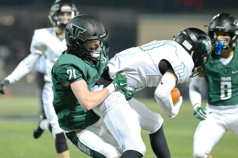 COURTESY PHOTO: CHRISTOPHER GERMANO - Tigard High School junior defensive back Hewitt Sullivan (left) tackles Century senior Chance Sparks during the Tigers' 56-20 playoff victory.