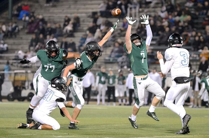 COURTESY PHOTO: CHRISTOPHER GERMANO - Tigard's (from left) Johnny Nomani, Kamryn Hosley and Cole Scott try to block a pass by Century quarterback Tyler Mahlman during the Tigers' 56-20 state playoff victory.