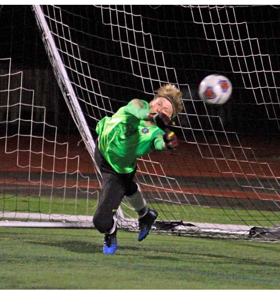 PMG PHOTO: WADE EVANSON - Summit goal keeper Khael Engleman knocks away a Forest Grove penalty kick during the Storm's state semifinal win over the Vikings Tuesday, Nov. 12, at Forest Grove High School.