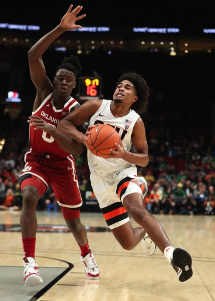PMG PHOTO: JAIME VALDEZ - Oregon State Beavers guard Ethan Thompson (right) drives on Oklahoma Sooners forward Victor Iwuakor in the first half Tuesday night at Moda Center.
