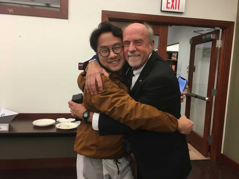 COURTESY PHOTO - Chen Yang embraces Mayor Russ Axelrod. Yang had just broken into an impromptu song expressing thanks for the opportunity to visit and share experiences.