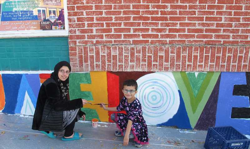 Aishah and Khadidja Mokrani, students at Markham Elementary, had never painted a mural before gettting instructions from Alex Cook.