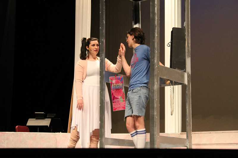 PMG PHOTO: GABBY URENDA - Forest Grove High School students play characters Clio (right) and Sonny (left) as they share a tender moment on stage during school musical 'Xanadu.'