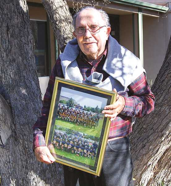 RAMONA MCCALLISTER - Jerry Pimentel pauses for a photo with the framed pictures of the two teams he proudly supported in recent years as a scorekeeper. He is photographed with the Crook County Middle School football team and the Crook County High School junior varsity team. The staff from CCMS presented the framed photos to him recently.