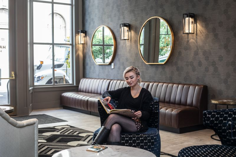PMG PHOTO: JONATHAN HOUSE - Desk clerk Emma Huen poses in the newly restored historical Harlow Hotel on the North Park Blocks. The owners wanted to open a budget hotel, but as historic preservation and engineering costs spiraled they had to upgrade to basic/boutique.