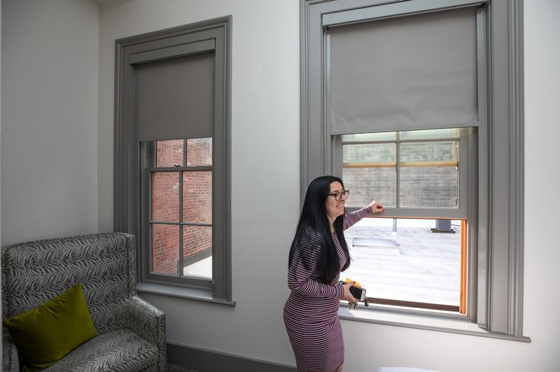 PMG PHOTO: JONATHAN HOUSE - Operations Manager Taylor Estrada shows off the original sash windows at the 1883-built Harlow Hotel. The view over the neighboring condo roof extends all the way to Big Pink.