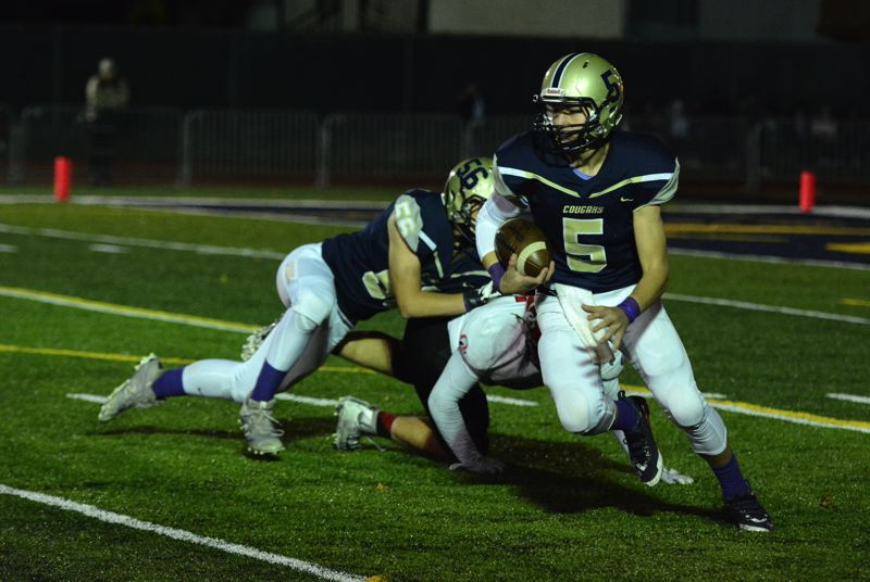PMG PHOTO: DEREK WILEY - Canby quarterback Mikey Gibson carries the ball for the Cougars during the 2019 season.
