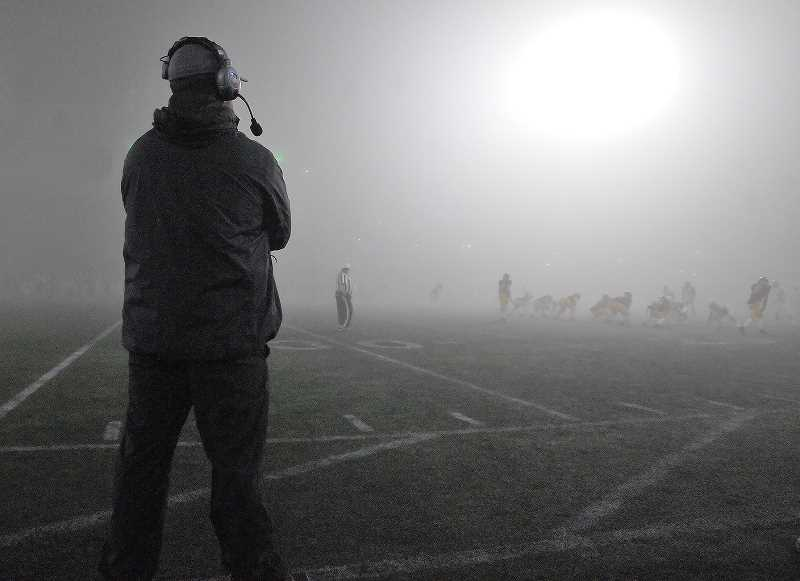 GRAPHIC PHOTO: GARY ALLEN - Thick fog descended on Hillsboro Stadium Friday evening, making it difficult for coaches like the Tigers' Kevin Hastin to monitor play during Central Catholic's win over Newberg.