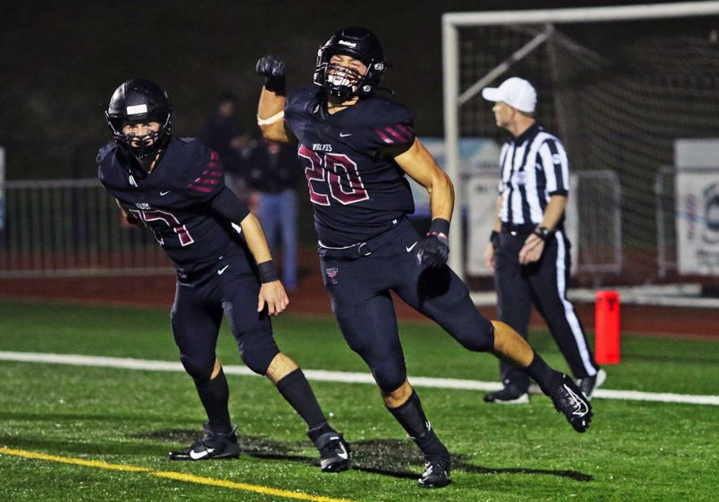 PMG PHOTO: DAN BROOD - Tualatin High School senior John Miller (20), with senior Blake Jackson next to him, celebrates after tackling North Medford junior Devin Bradd for a safety during the Wolves' 50-35 state playoff win.