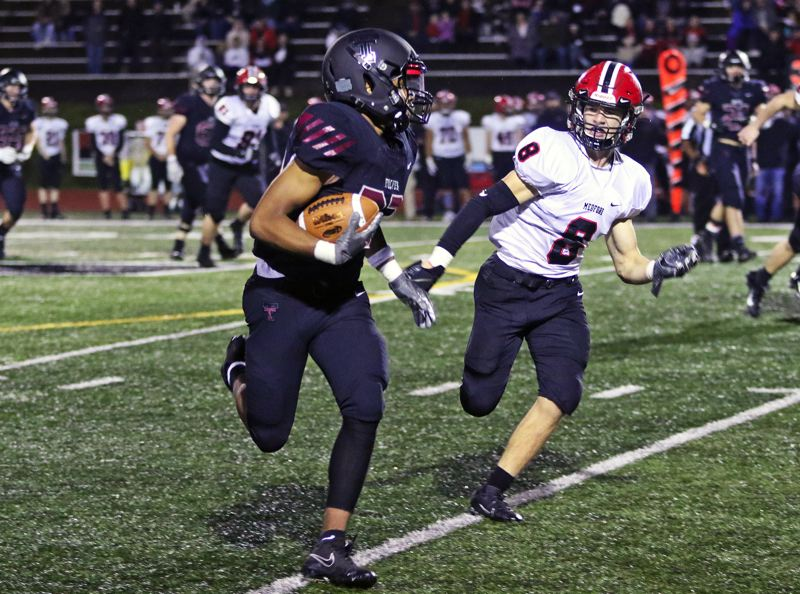 PMG PHOTO: DAN BROOD - Tualatin High School sophomore Malik Ross (left) looks to get by North Medford senior Cole Zoller on his way to gaining 32 yards on a pass play in the Wolves' 50-35 state playoff win.