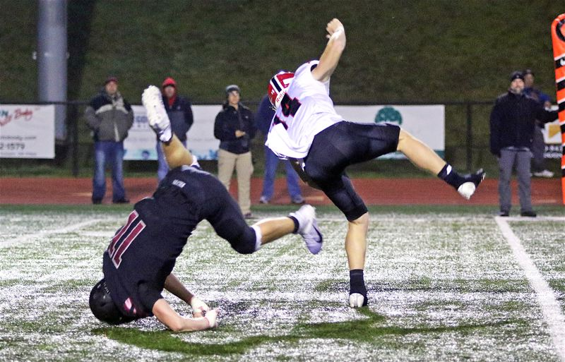 PMG PHOTO: DAN BROOD - Tualatin High School senior Jake Reser (11) hits the turf after blocking a punt by North Medford junior Colby Neron during Friday's Class 6A state playoff second-round game.