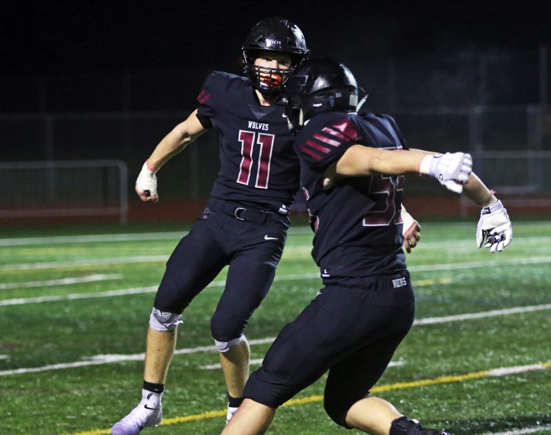 PMG PHOTO: DAN BROOD - Tualatin High School senior Jake Reser (11) gets ready to celebrate with senior Cody Van Meter after blocking a North Medford punt in the Wolves' 50-35 state playoff win on Friday.