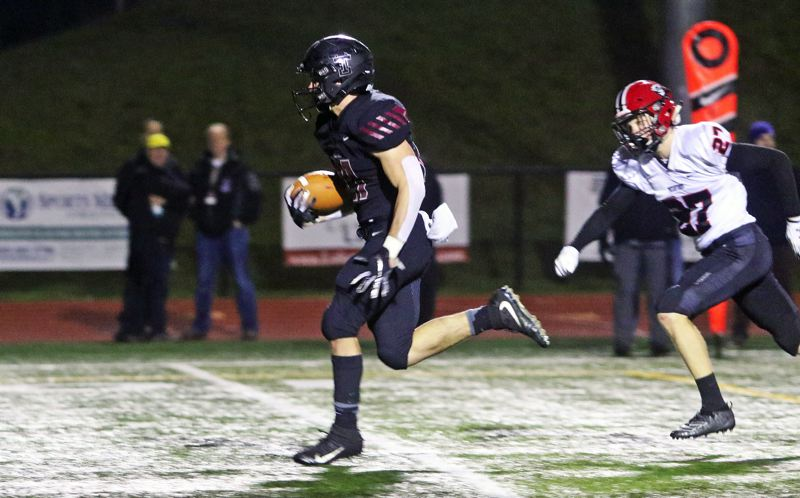 PMG PHOTO: DAN BROOD - Tualatin High School senior Kainoa Sayre (left) breaks past North Medford junior Nolan Morris, and into the clear, on his way to scoring on a 24-yard run in the Wolves' 50-35 win.